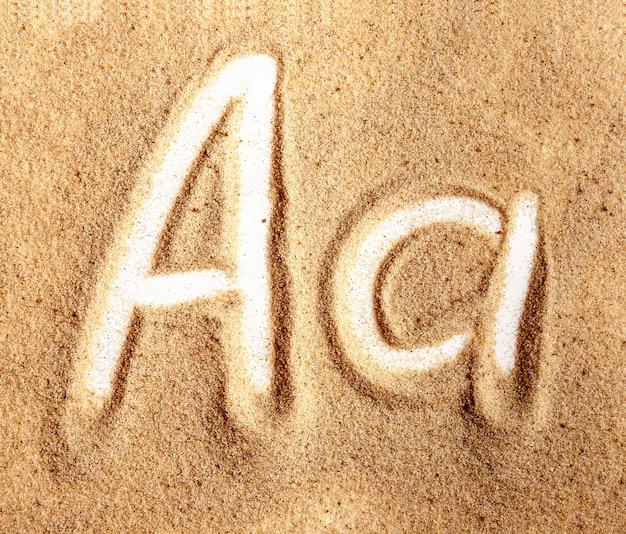 Buchstabe ein englisches handgeschriebenes alphabet im sand