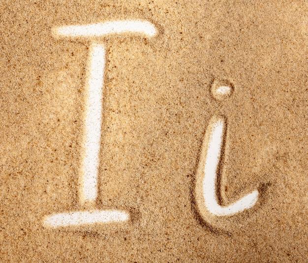 Buchstabe i englisches handgeschriebenes alphabet im sand