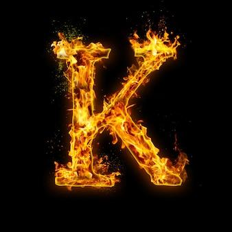 Buchstabe k. feuerflammen auf schwarzem, realistischem feuereffekt mit funken. teil des alphabetsets