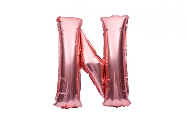 Buchstabe n aus roségoldenem aufblasbarem heliumballon, isoliert auf weiß. goldrosa folienballonschriftteil des vollständigen alphabetsatzes der großbuchstaben.