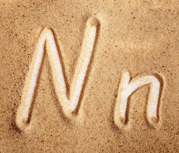 Buchstabe n englisch handgeschriebenes alphabet im sand