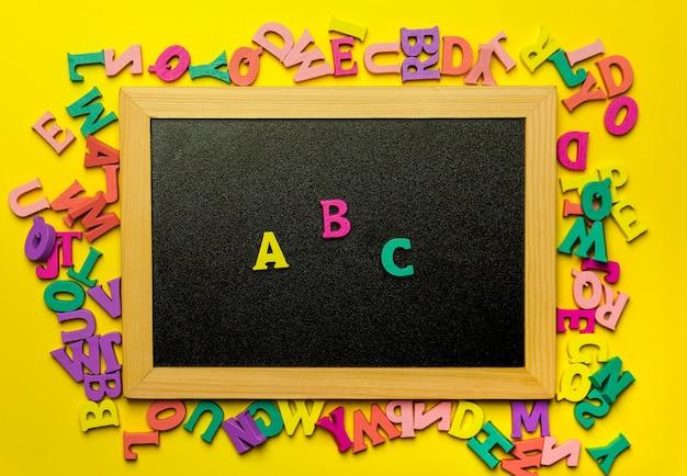 Buchstaben abc an der tafel, umgeben von holzbuchstaben.