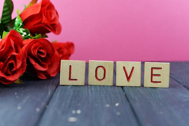 Buchstaben aus holz mit der textaufschrift liebe mit rotrose