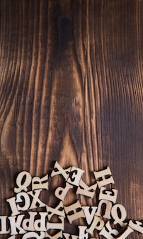 Buchstaben des englischen alphabets auf einem dunklen hölzernen hintergrund. das konzept von bildung, wortspielen, handarbeiten. platz für text