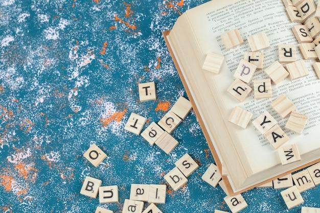 Buchstabendominos aus holz und isoliert auf der blauen musteroberfläche