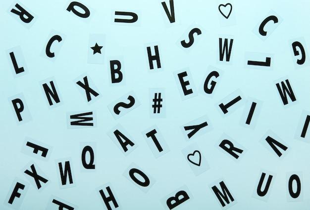 Buchstabenhintergrund, nahaufnahme vieler zufälliger buchstaben und symbole auf blauem hintergrund.
