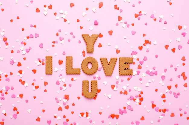Buchstabeplätzchen ich liebe dich mit den rosa und roten herzen auf rosa