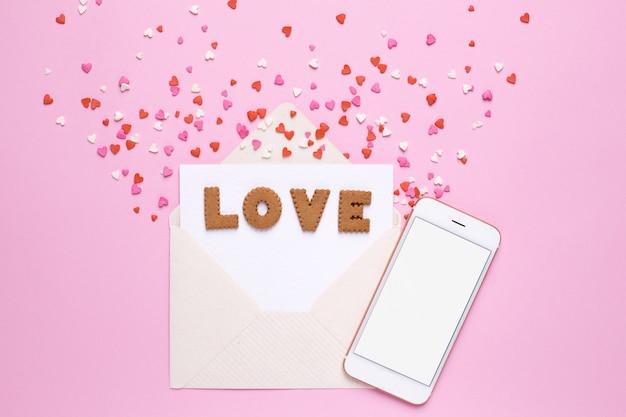 Buchstabeplätzchen lieben mit umschlag und roten herzen auf rosa