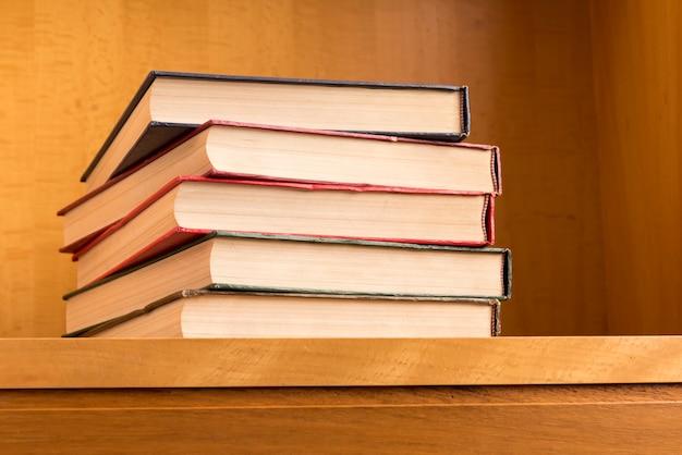 Buchstapel auf hölzernem schreibtisch im klassenzimmer.