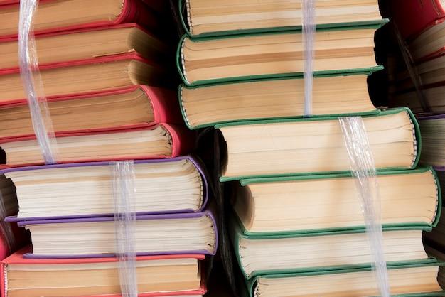 Buchstapel auf hölzernem schreibtisch in der bibliothek.