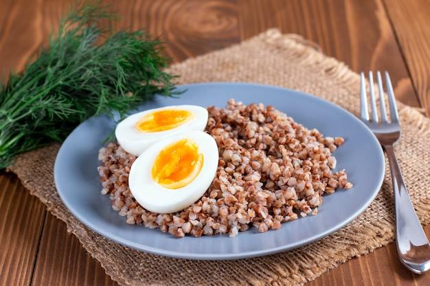 Buchweizen mit gemüse auf einem hölzernen hintergrund. gesundes frühstück mit ei, gurke und buchweizenbrei. diätmenü.