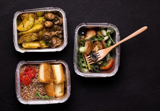 Buchweizen mit käse, salat, kartoffeln und pilzen in einem folienbehälter. lebensmittellieferservice