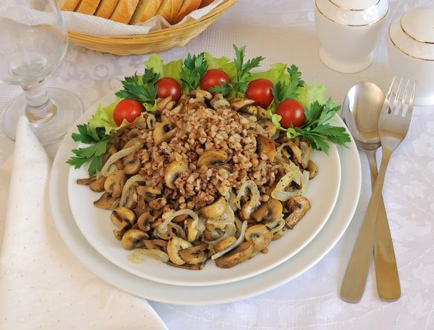 Buchweizenbrei mit champignons und zwiebeln auf dem esstisch