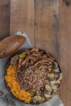 Buchweizenbrei mit rindfleischstücken, pilzen und karotten. draufsicht der nahrungsmittelplatte auf hölzernem hintergrund mit kopienraum.
