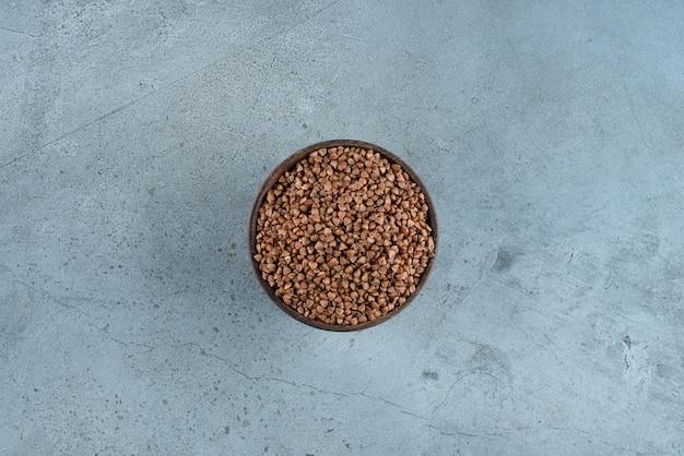 Buchweizenkörner in einer holzschale auf blauem hintergrund. foto in hoher qualität