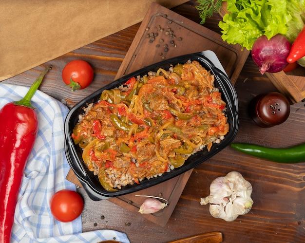 Buchweizenmahlzeit zum mitnehmen im schwarzen plastikbehälter, diätetisches lebensmittel mit gebratener soße der grünen pfefferzwiebel der tomate