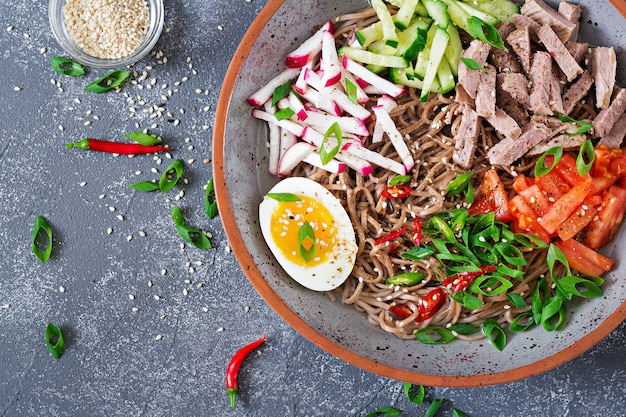 Buchweizennudeln mit rindfleisch, eiern und gemüse. koreanisches essen. buchweizennudelsuppe. oben