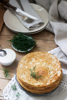 Buchweizenpfannkuchen serviert mit saurer sahne und dill auf einem holztisch. rustikaler stil.