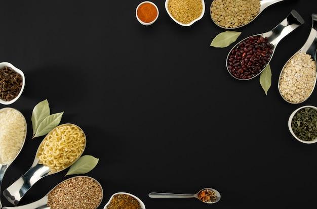 Buckwheat krupp linsen reis pasta bohnen gewürze in löffel bucht blatt auf dunkel
