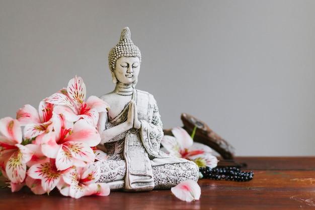 Buda-skulptur mit blütenblättern