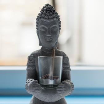 Buddha aus zement mit glas mit münzen und einem bleistift