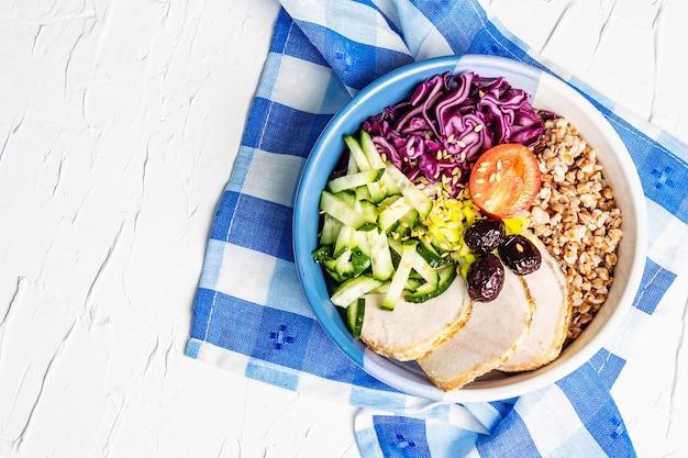 Buddha bowl. buchweizen, gebackenes mageres schweinefleisch, rotkohl, gurke, tomate, oliven, leinsamen.