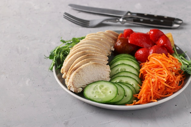 Buddha bowl mit gebackenem huhn, frischer gurke, erbsen-mikrogrinen, karotten und paprika auf einem grauen betonhintergrund. konzept für saubere und ausgewogene gesunde ernährung