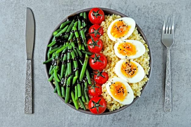 Buddha-schale mit bulgur, grünen bohnen, kirschtomaten und gekochten eihälften. gesundes essen in einer schüssel. das konzept der diätetischen ernährung.