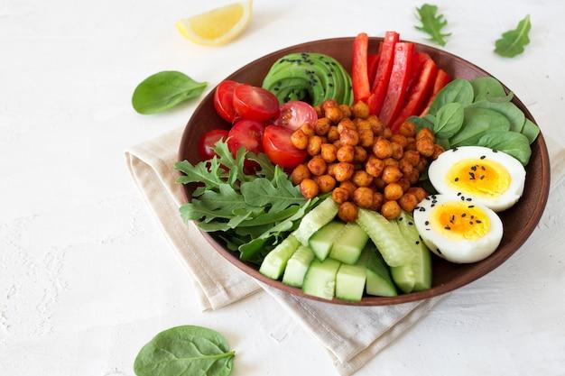 Buddha-schüssel, gesundes und ausgewogenes essen. gebratene kichererbsen, kirschtomaten, gurken, paprika, eier, spinat, rucola