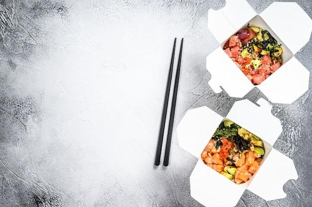 Buddha-schüssel in papierbox mit gemüse, lachs und thunfisch. straßenessen zum mitnehmen.