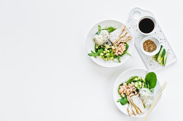 Buddha-schüssel mit glasnudeln, bohnen, hühnerbrust, spinat, rucola und gurke