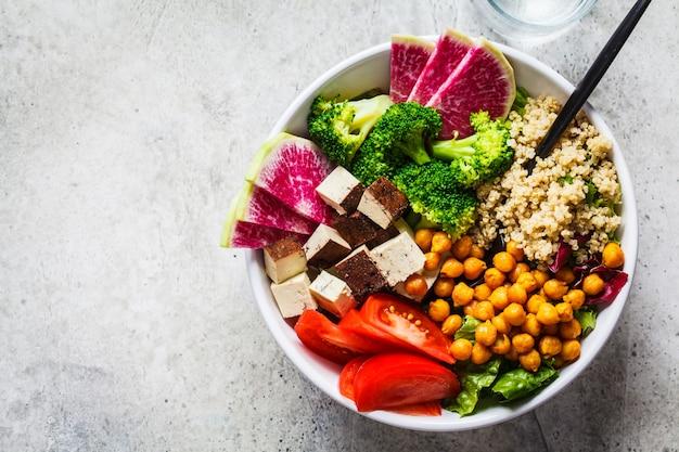 Buddha-schüssel mit quinoa, gebratenen kichererbsen, geräuchertem tofu und gemüse in der weißen platte