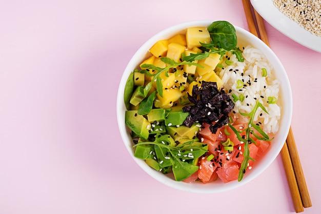 Buddha schüssel mit reis, mango, avocado und lachs. gesundes lebensmittelkonzept.