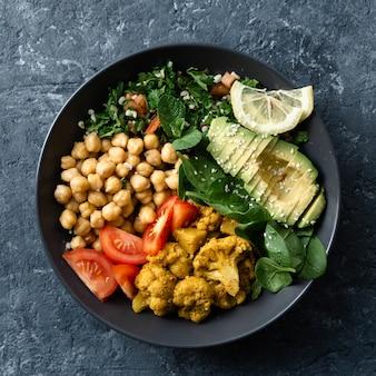 Buddha-schüssel vegetarisches gesundes ausgewogenes essen aloo-gobi, kichererbsen, tomate, avocado, tabulesalat und spinat