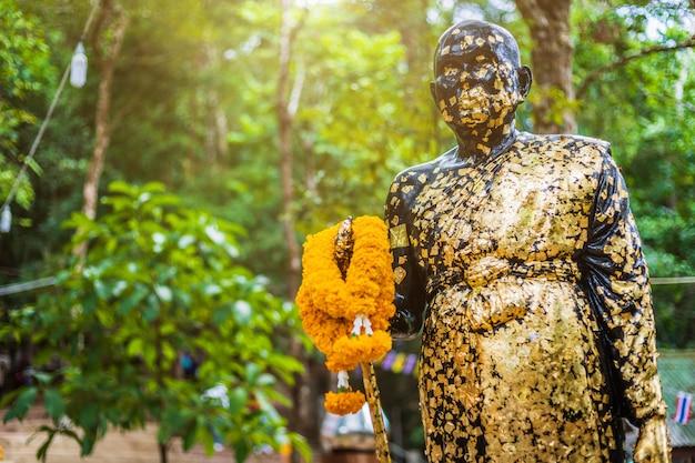 Buddha-statue auf dem weg zum stein mit dem fußabdruck von lord buddha