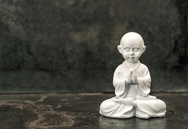 Buddha-statue auf dunklem hintergrund. betender weißer mönch. meditationskonzept. getöntes bild im vintage-stil