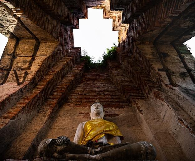 Buddha-statue, die auf sockeln mit alter antiker backsteinmauer hinter dem tempel mit ruinen von ayutthaya thailand sitzt