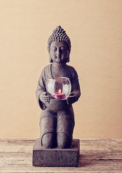 Buddha-statue mit einer brennenden kerze in seinen händen