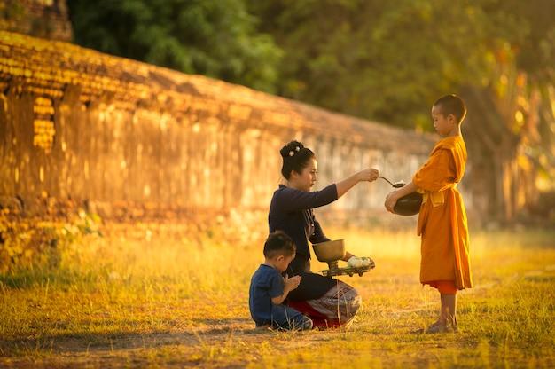 Buddhisten verdienen am morgen nach den prinzipien des buddhismus und bringen nahrung zu den mönchen, deren mönche segnen werden.