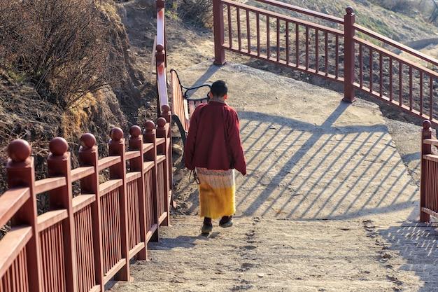 Buddhistische nonne, die hinunter treppenhaus bei larung gar in einer warmen und nebeligen morgenzeit, sichuan geht