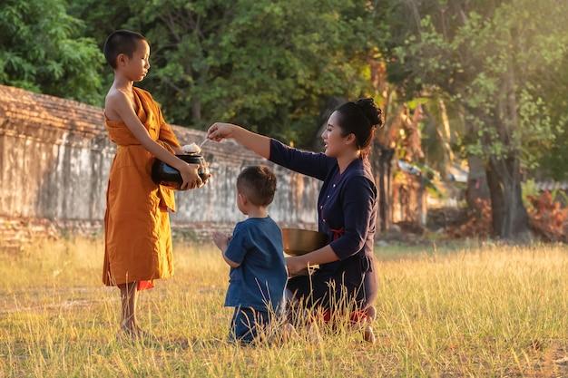 Buddhistischer älterer anfänger. die familie kinderfrau, die speiseangebote in die almosenschale eines mönchs legt, und eine frau, die sich niederwirft, um anbetungsmönche zu respektieren, mönche, die jeden morgen routine gehen.