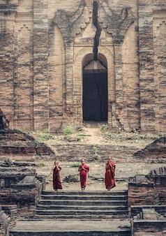 Buddhistischer anfänger betet in mingun pahtodawgyi (mingun paya), myanmar