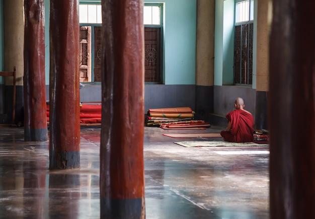 Buddhistischer mönch, der an der ruhigen ecke der kapelle meditiert