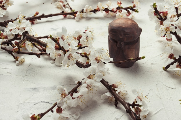 Buddhistischer mönch der kleinen statuette und ein zweig von kirschblumen auf einer hellen steinoberfläche. konzept der frühlingsferien und des neuen jahres für den asiatischen kalender