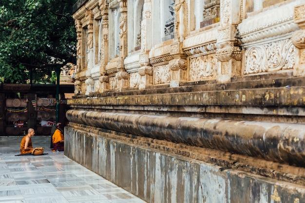 Buddhistischer mönch in der meditation unter bodhi-baum im bereich des mahabodhi-tempels