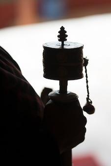 Buddhistischer pilgerer mit gebetsrad in drepung-kloster, lhasa, tibet, china