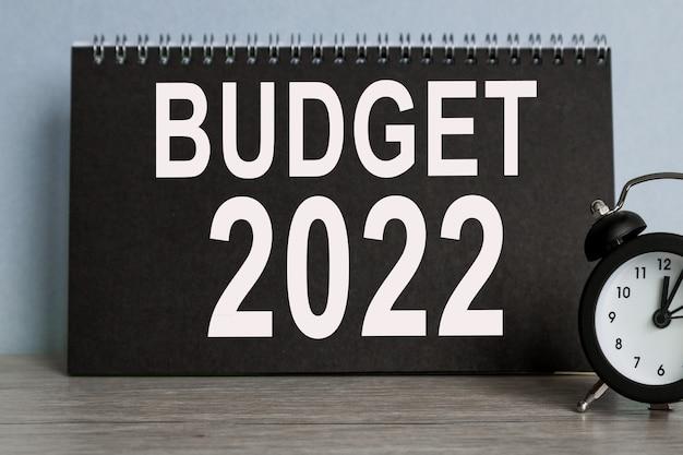 Budget 2022, wecker, schwarzes notizbuch mit text, auf blauem hintergrund, zeit läuft davon.