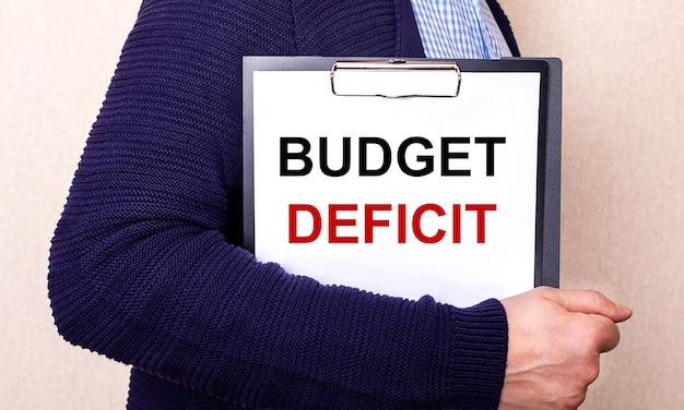 Budget deficit steht auf einem weißen blatt, das von einem seitlich stehenden mann gehalten wird