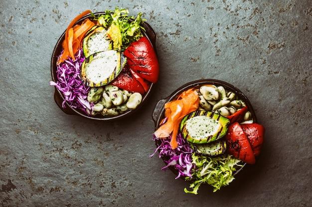 Budha schüssel. rohes gemüse mit bohnen, gegrillter avocado und grünem pfeffer auf schieferhintergrund. ansicht von oben