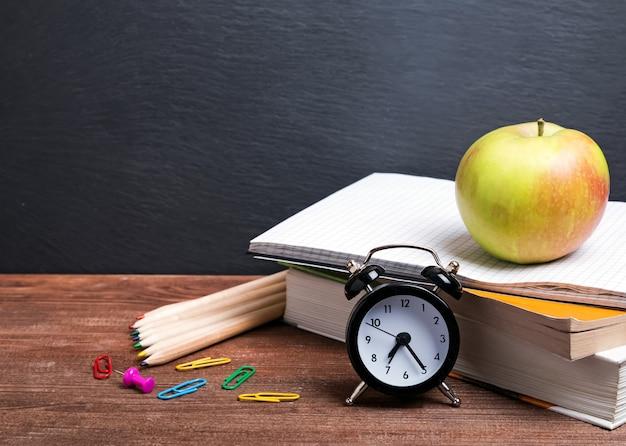 Bücher, apfel und uhr und andere schulsachen auf dem holztisch.